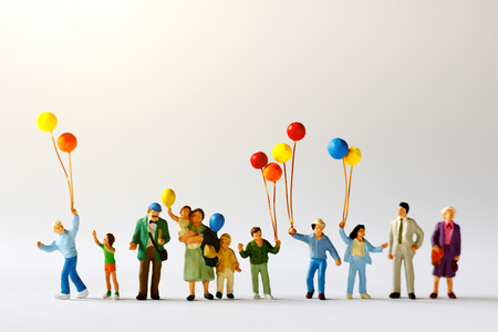 Foto de Miniature people with family holding balloon  on the map with sunlight, happy family day concept. - Imagen libre de derechos