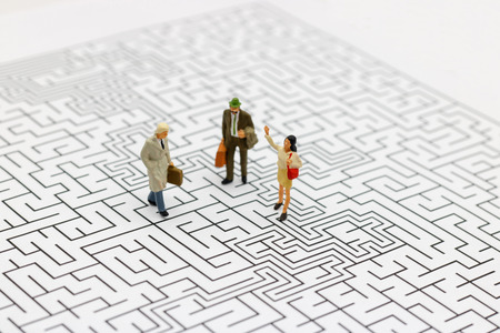Miniature people: Business team standing on center of maze