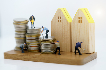 Photo pour Miniature people: Workers working with tools on coins stack with wood house. Renovation and property service concept. - image libre de droit
