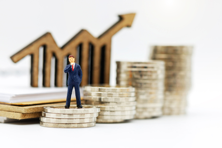 Photo pour Miniature people:  Businessmen standing on coins stack with graph, Finance, investment and growth in business concept. - image libre de droit