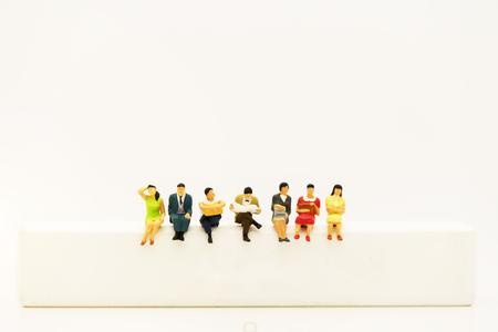 Photo pour Miniature people: Business team reading book on white wooden box. - image libre de droit