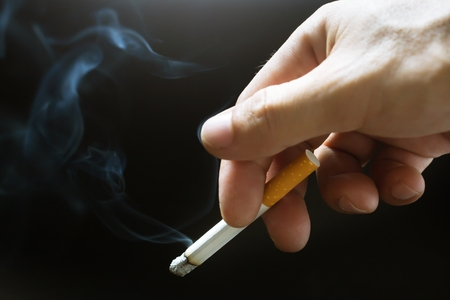 Photo for The man smoking a cigarette in hand. Cigarette smoke spread. - Royalty Free Image