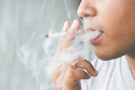 Photo pour man smoking a cigarette. Cigarette smoke spread. - image libre de droit