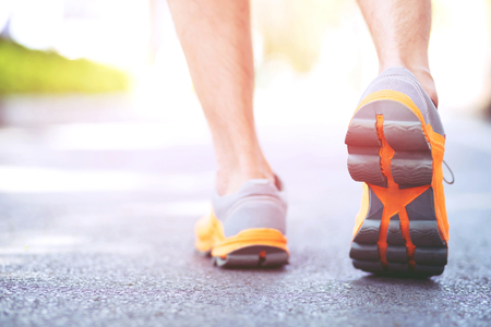 Foto de close up shoe fitness people runner athlete running at on road at sunrise in public park. Fitness and exercise workout wellness concept. soft focus. - Imagen libre de derechos