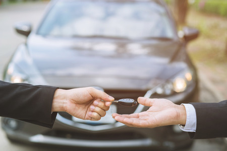 Photo pour Car key, businessman handing over gives the car key to the other woman on showroom background. - image libre de droit