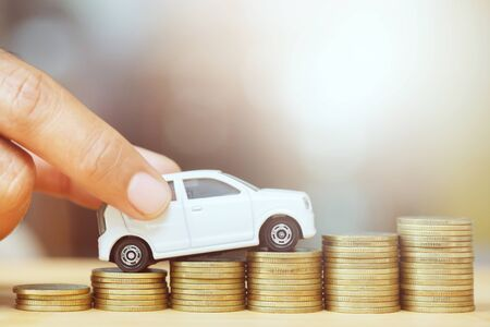 Photo for Business man and close up hand holding model of toy car on over a lot money of stacked coins - insurance, loan and buying car finance concept. buy and installments down payment a car. - Royalty Free Image