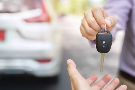 Photo pour Car key, businessman handing over gives the car key to the other man on car background. - image libre de droit