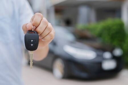 Photo pour Business man hand holding car keys front with new car on background. parking in front of the house. transportation concept. Leave copy space to write messages text. - image libre de droit