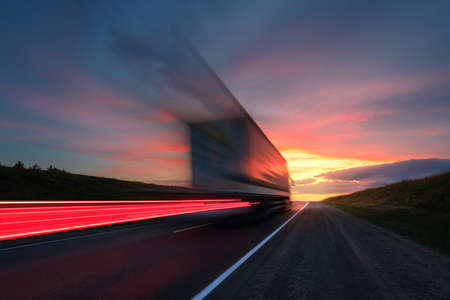 Photo for Blurring. A large truck is driving along the highway at high speed. Sky with bright red clouds. Delivery of cargo. - Royalty Free Image