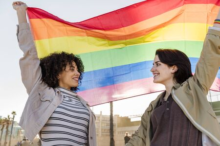 Foto de interracial lesbian couple of smiling girls waving the rainbow flag, symbol of the struggle for gay rights, concept of sexual freedom and racial diversity - Imagen libre de derechos