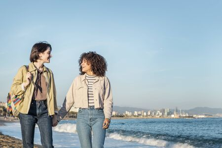 Photo pour young couple of gay women walking holding hands and looking into each other's eyes in Barcelona, gay friendly city, with the colors of the rainbow flag, concept of sexual freedom and racial diversity - image libre de droit