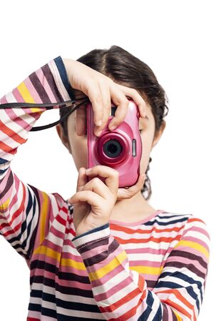 Photo for vertical photo of a little girl isolated on a white background taking pictures with her pink camera, concept of children and their hobbies - Royalty Free Image