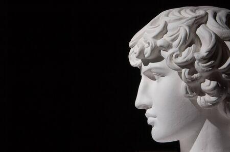 Plaster head of sculpture, black background