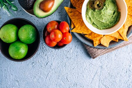 Bowl with Mexican guacamole on vintage wooden table, surrounded by tomatoes, jalapeños peppers, limes and avocados. Copyspace
