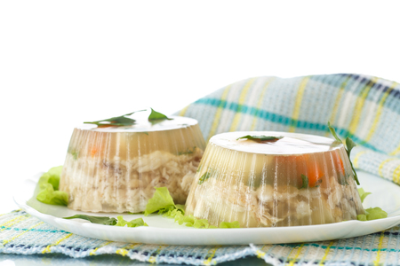 Jellied fish with egg and vegetables on a white background