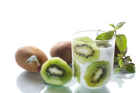Sweet milk organic yogurt with slices of kiwi on white background