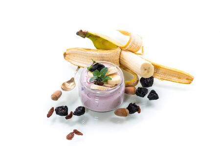 Photo for Sweet tasty yogurt with banana, prunes, raisins in a glass jar on a white - Royalty Free Image