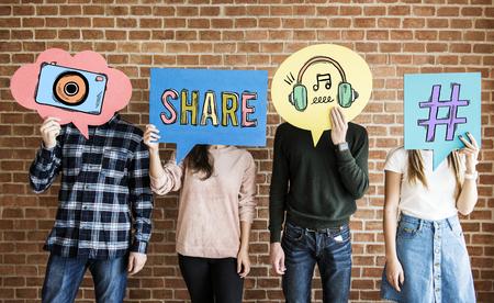 Photo pour Friends holding up thought bubbles with social media concept icons - image libre de droit