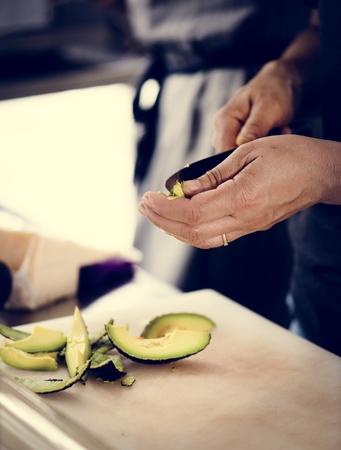 Closeup of hands peeling avocado