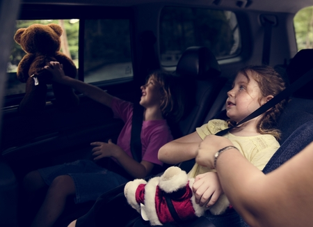 Young girls sitting inside a car