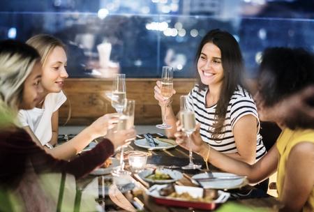 Photo pour Girl friends having a dinner together at a rooftop bar - image libre de droit