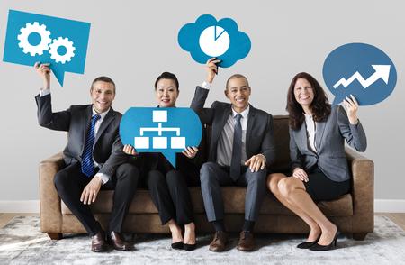 Photo pour Diverse business people holding speech bubbles with development icons - image libre de droit