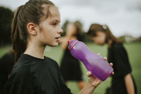 Photo pour Female football player drinking from a water bottle - image libre de droit