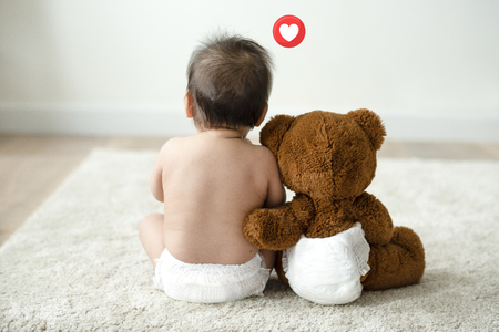 Photo for Toddler sitting beside his teddy bear - Royalty Free Image