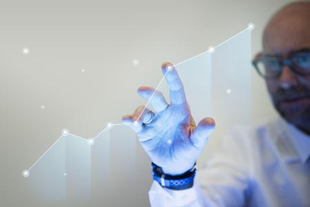 Photo pour Businessman pointing his finger to a growth graph - image libre de droit