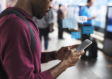 Photo pour Black man using mobile phone at a platform - image libre de droit