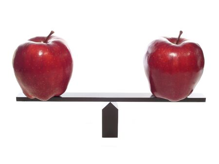 Comparing apples to apples on a balance beam, isolated on white