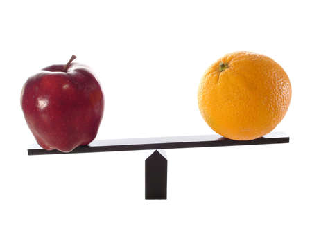 Metaphor of comparing apples to oranges on a balance beam isolated on white and the oranges are not as heavy or light.