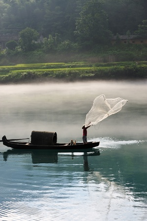 A fisherman casting his net from the boat on the river