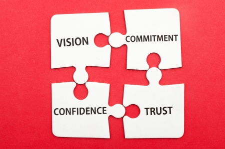 Business teamwork concept of vision, commitment, confidence, trust written on group of jigsaw puzzle pieces