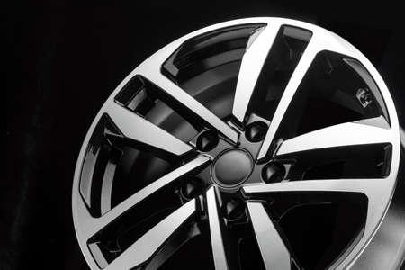 Photo pour new shiny alloy wheel on black background, close-up details - image libre de droit