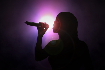Women singing with microphone under spotlight