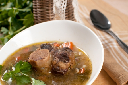 Ox tail soup with barley and parsley close-up