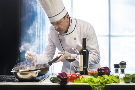 Photo pour Cook preparing roast meat with vegetable in the pan - image libre de droit