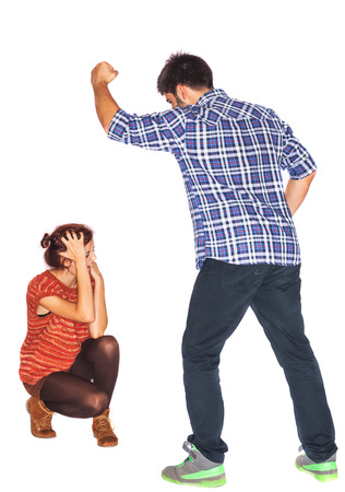 Frightened and crying woman next to angry husband holding his fist upwards - domestic violence - isolated on white