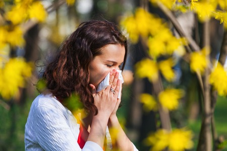 Young woman blowing her nose while being in the nature