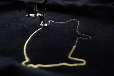 Photo pour Embroidery machine stitching pig motive with precious gold yarn on black velvetely fabric- 2019 chinese new year concept - side view with blurred foreground and background - image libre de droit