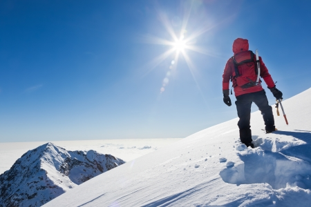 Mountaineer reaches the top of a snowy mountain in a sunny winter day  Western Alps, Biella, Italy