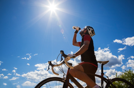 Cyclist resting and drinking isotonic drink  Backlight, sunny summer day