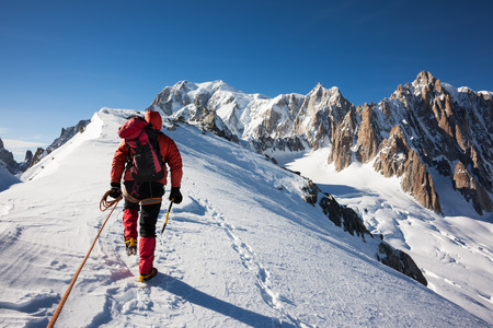 Mountaneer climbs a snowy ridge in Mont Blanc, France  Enterprise, diligence, team work  mountaneering concepts