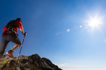 Skyrunner runs uphill along a mountain trail. Rear way, caucasian young man. Sunny summer day. West Alps, Europe.