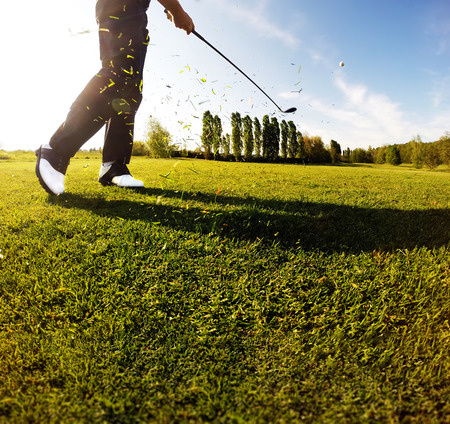 Golf swing on the course. Golfer performs a golf shot from the fairway. Sunny summer day. Concept: sport, relax, tourism, welfare.