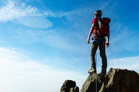 Photo pour Climber arrive on the summit of a mountain peak. Concepts: victory, success, achievement, triumph. - image libre de droit