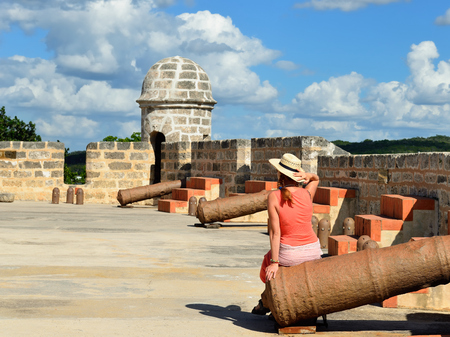 The tourist touring the Jagua fort is sitting on the ancient cannon. Fort built by Spaniards by the Cienfuegos city on Cuba.In the assumption he was supposed to defend the access to the Cienfuegos bay against assaults with pirates