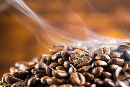 pile of hot coffee beans with smoke