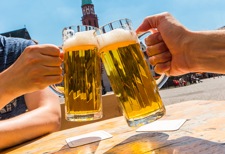 two human hands toast with glasses of German beer in Frankfurt
